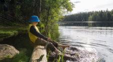 En pojke sitter vid en sjö i Finland och skvätter vatten med fötterna. Han lever i värdens lyckligaste land, enligt en ny FN-rapport