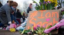 En kvinna lägger blommor vid en minnesmanifestation för Sarah Everard i Storbritannien.