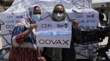 Två kvinnor med munskydd håller uppe en skylt med COVAX.
