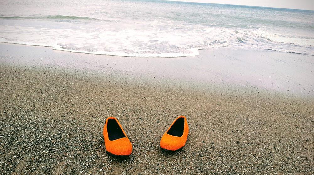 Skor från Pine Kazi som har tillverkats av skal från ananas står på en sandstrand.