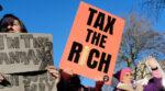 """Demonstranter protesterar i London 2020 med skyltar """"Tax the rich""""."""